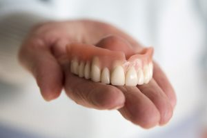 Hand holding dentures in Temple